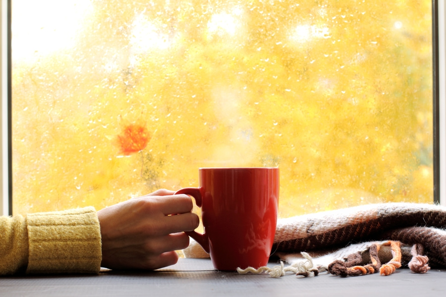 red mug of hot drink, when behind a window is rain in autumn in Fort Smith, AR